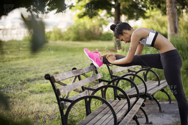 Female athlete stretching leg on park bench