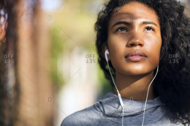 Woman in running hoodie listening to earbuds