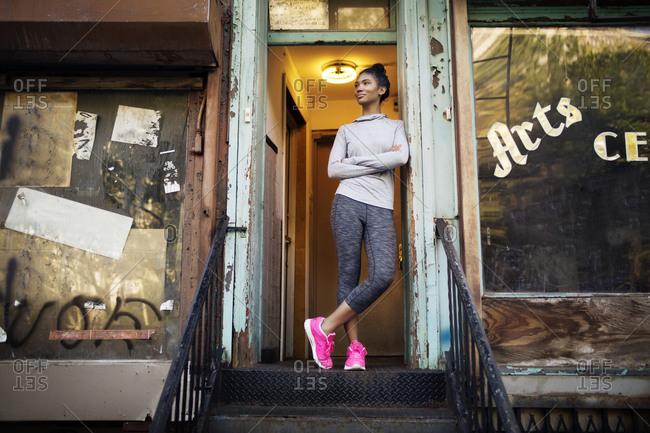 Female athlete standing in doorway of rundown building
