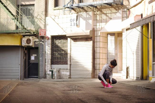 Female athlete tying shoe in alleyway