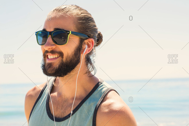 Hipster with headphones and shades at the beach