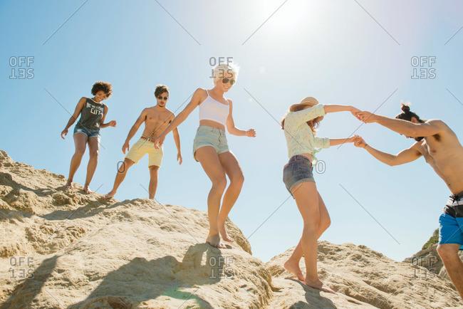 Group of friends climbing down dunes to beach