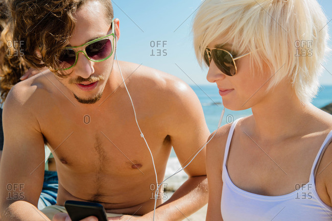 Young couple listening to music together at the beach