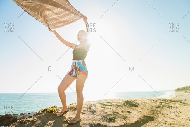 Young woman with towel blowing in wind at the beach