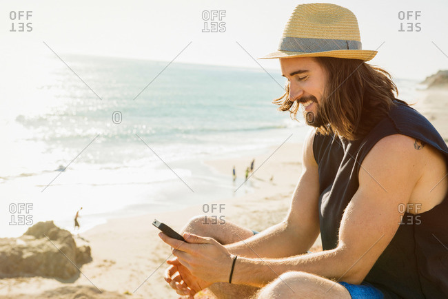 Young man using a smartphone at the beach