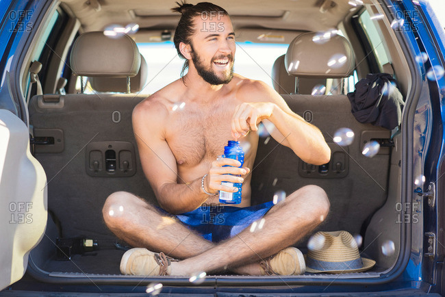 Young man sitting in a car after a day at the beach