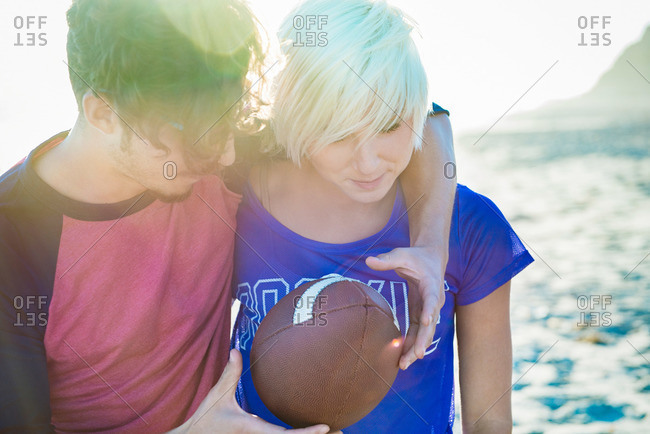 Young romantic couple with a football at the beach