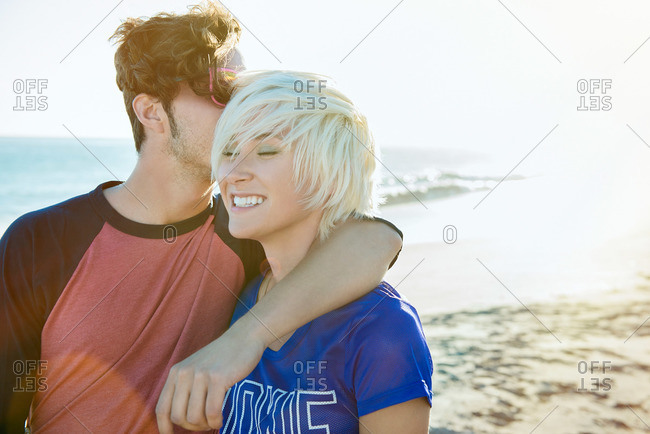 Young man kissing his girlfriend at the beach