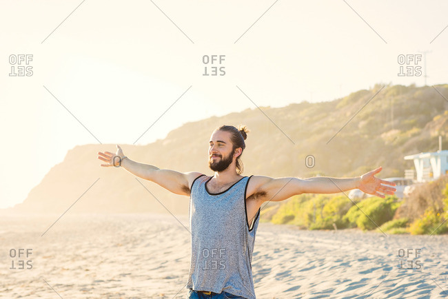 Young man with arms spread at the beach
