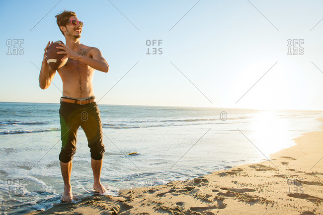 Young man throwing a football at the beach