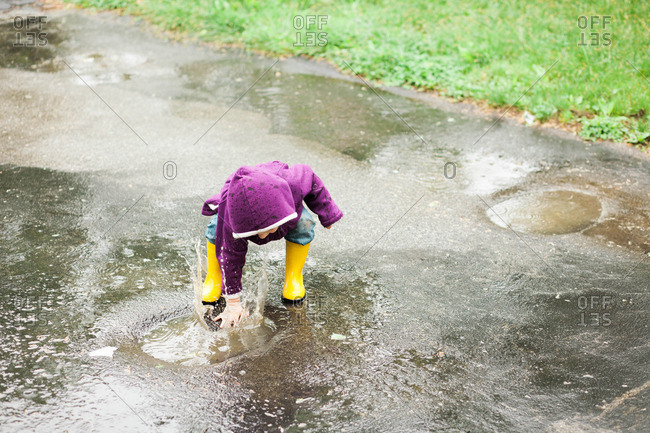 Girl playing in a rain puddle on concrete