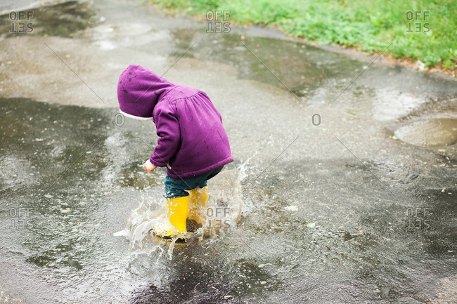 Girl playing in a rain puddle on pavement