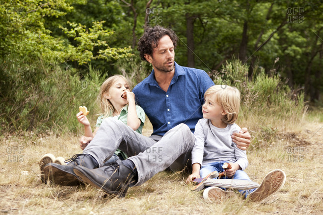 Father with two children having a picnic at forest edge
