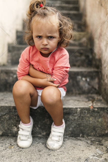 Portrait of little girl sitting on steps pouting mouth