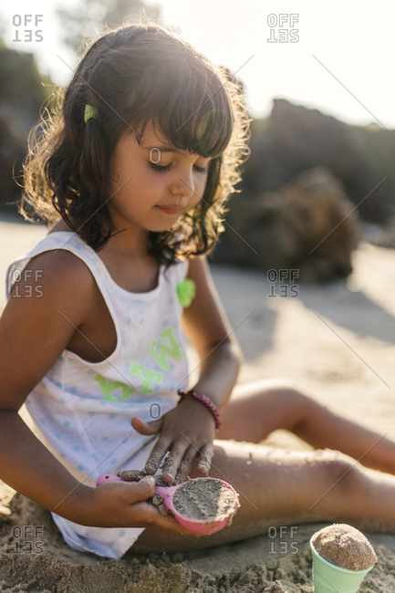 Little girl playing with sand on the beach, Llanes