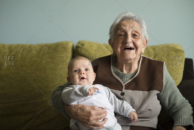 Portrait of great-grandmother sitting on a couch with her great-grandson