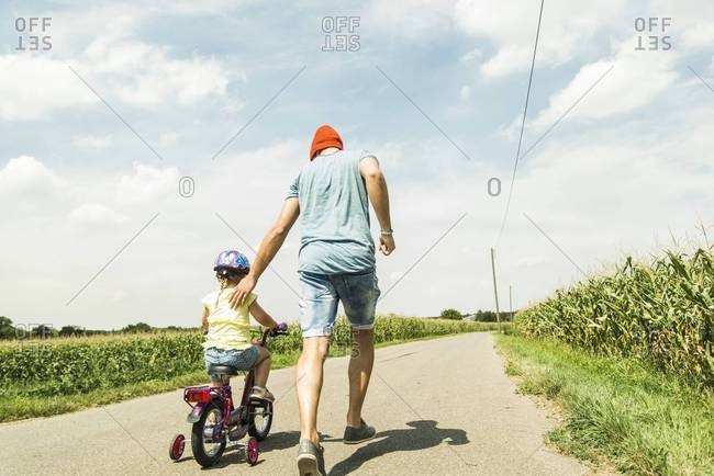 Father supporting daughter on bike