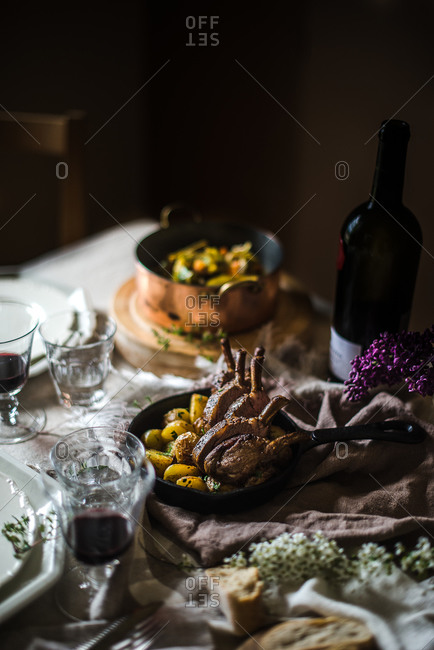 Potatoes and rack of lamb on set table