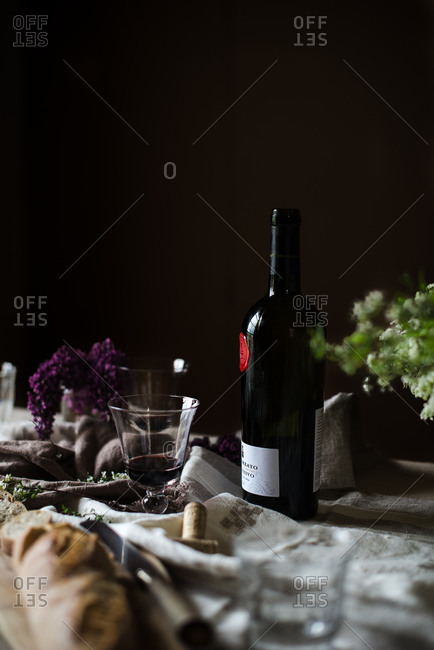 Table set with red wine bottle and glasses
