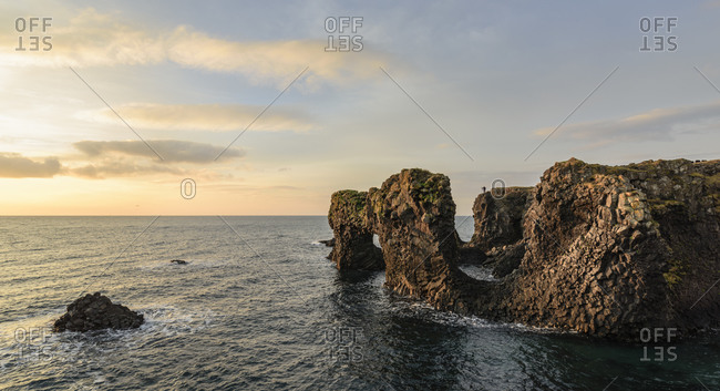 Photographer above coastal rock formations in Snaefellsnes, Iceland