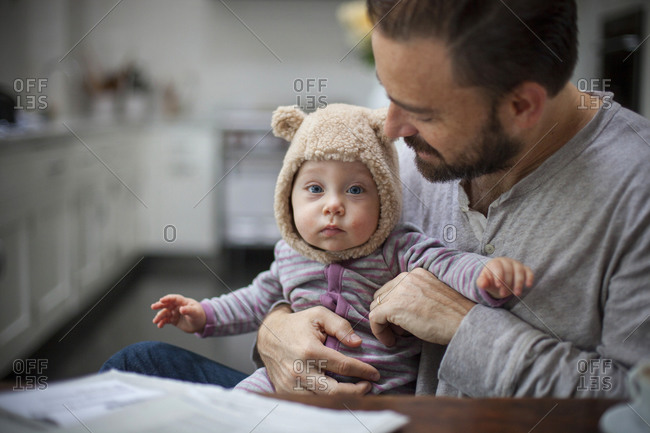 A baby in a bear hat being  held by her father who gazes at her lovingly