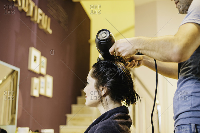 Young woman getting her hair dressed in hair salon