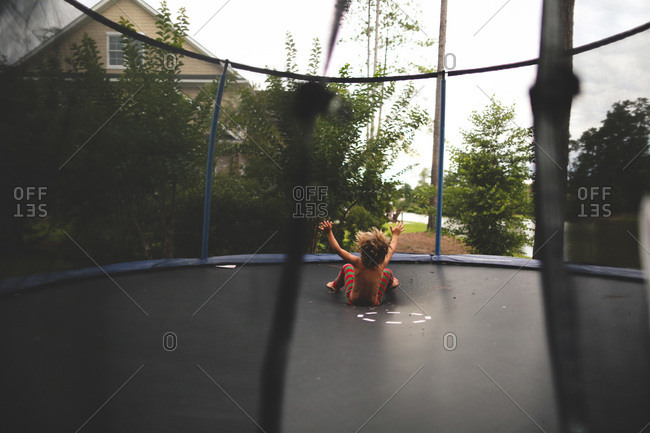 Boy falling onto trampoline while jumping