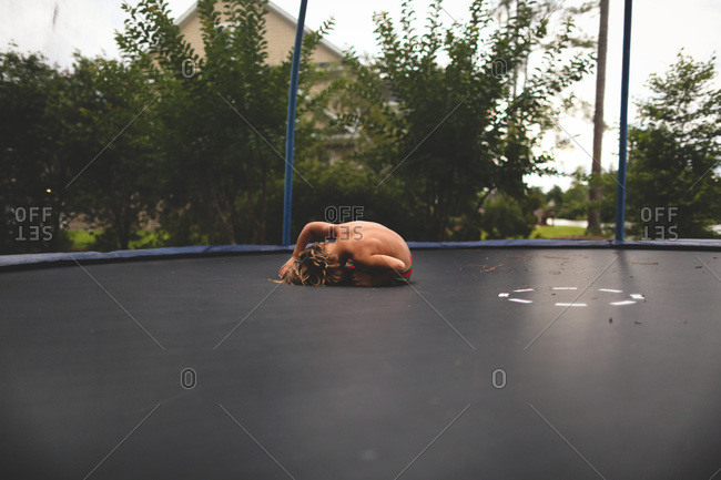 Boy laying on trampoline after jump