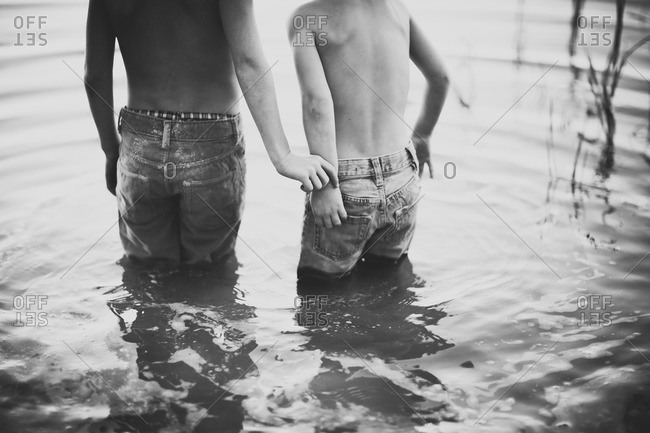 Two boys in jeans standing in water
