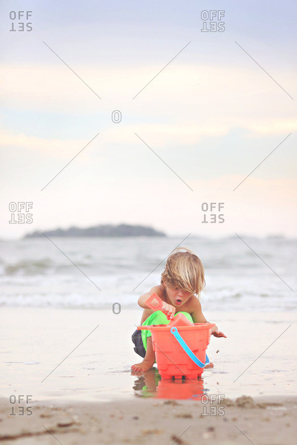 Boy digging in the sand on beach with bucket