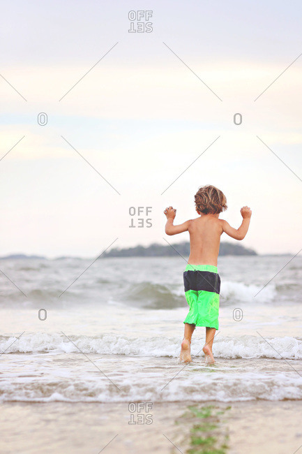 Little boy jumping in the surf on beach