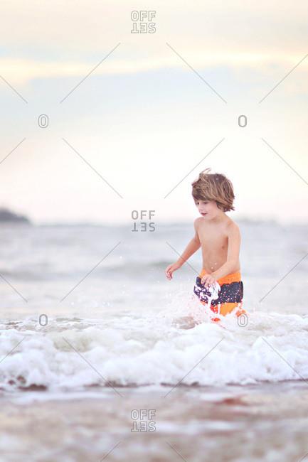 Little boy splashing around in the ocean