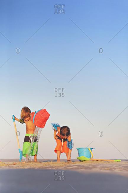 Two boys on a beach with beach toys