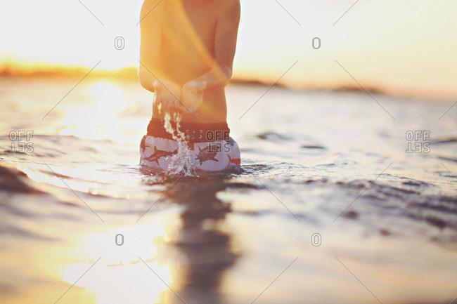 Midsection of boy splashing water in ocean