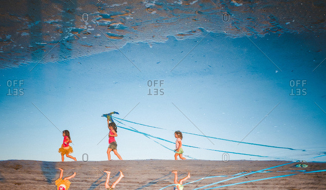 A reflection of children walking on the beach
