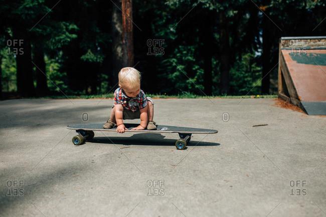 A baby boy balances on a skateboard
