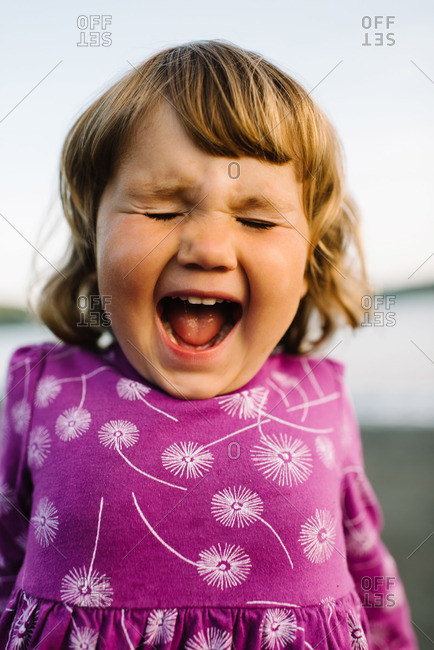 A young girl screams on the beach
