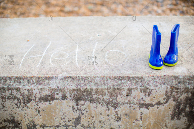 Galoshes on concrete ledge with message