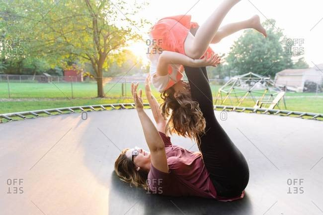 Mom lifting kid with legs on trampoline