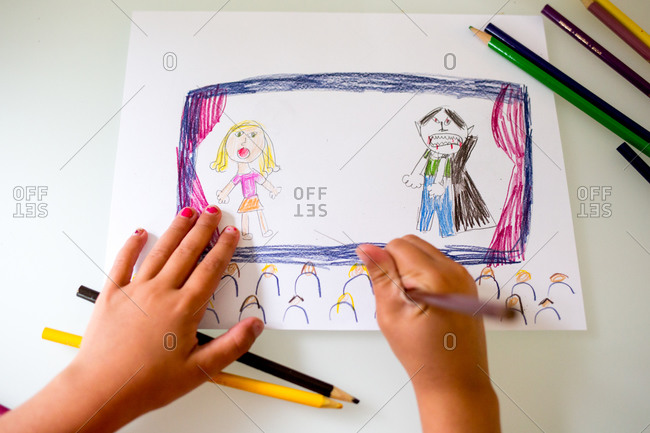 A girl draws a picture of a girl and a vampire