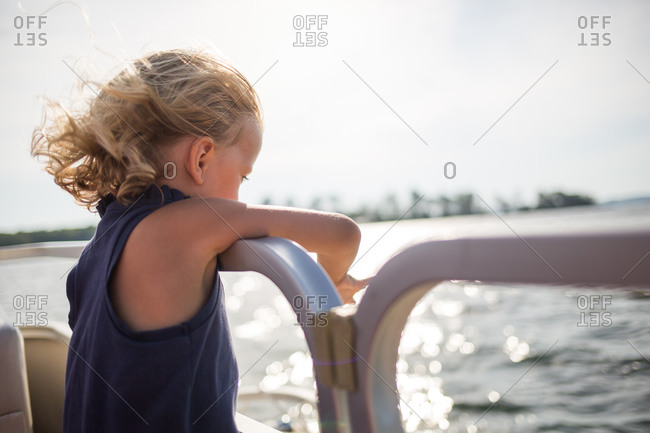 A girl looks over the edge of a boat