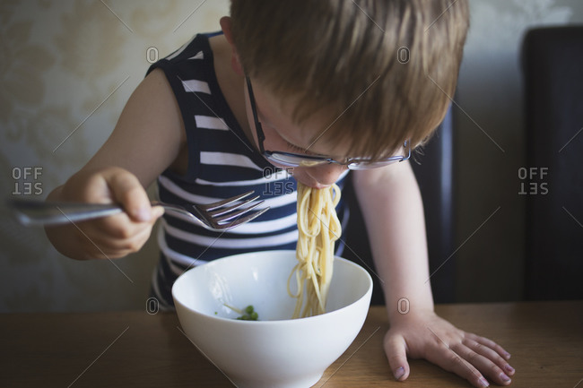 Boy eating pasta at dining table