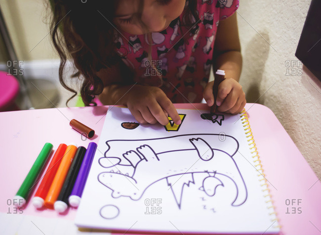 Girl coloring with markers stock photo - OFFSET