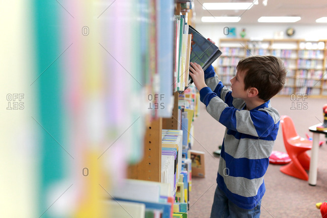 A boy pulls books from a library shelf