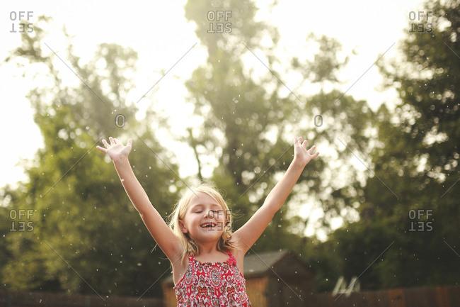 A girl in yard during sun shower
