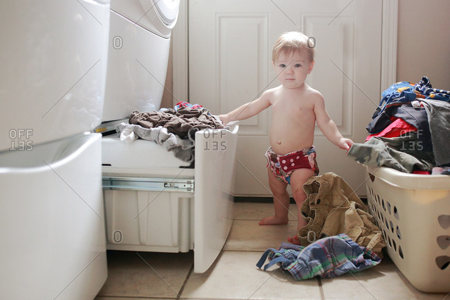 A little girl empties laundry from a machine