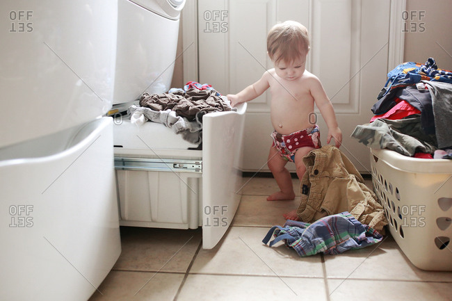 A little girl drops laundry on the floor