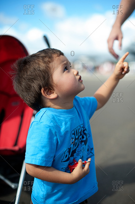 A boy points to the sky while holding a toy plane