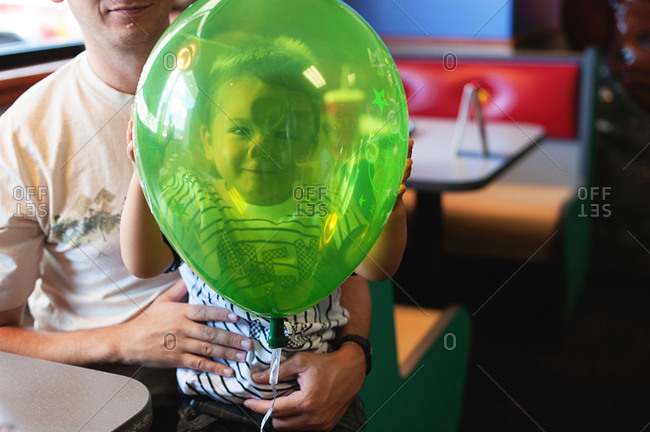 A boy presses his face against a balloon