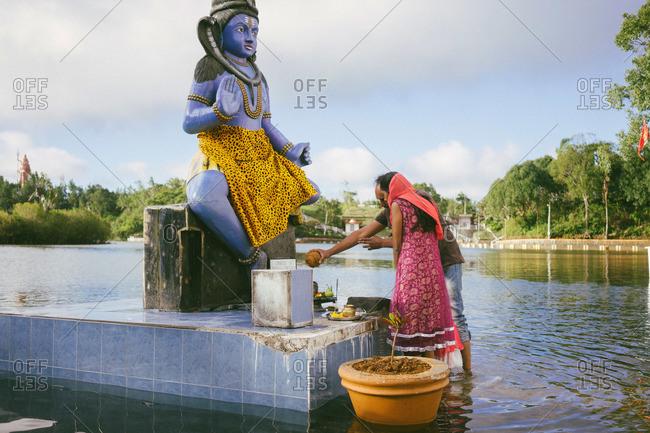 Savanne, Mauritius - March 20, 2015: Couple making offerings at a Shiva statue at Ganga Talao, Mauritius